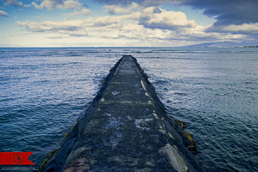 The distant ocean horizon of Waikiki beach in Hawaii skyline off a stone pier.