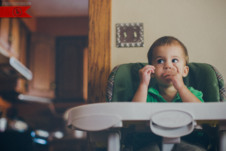 Little boy eating cheerios in a highchair outside the kitchen.