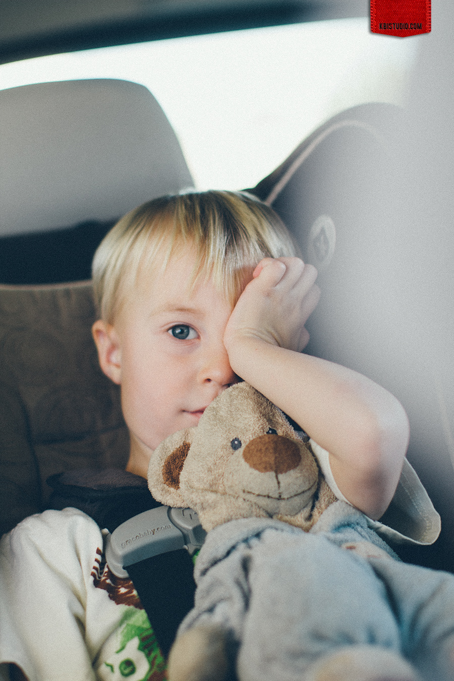 Boy with teddy bear wakes up after nap in his car seat